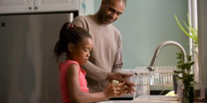 A father and daughter wash their hands at the kitchen sink