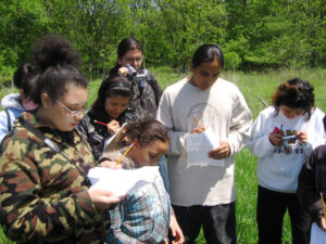 Group of mixed age kids writing outdoors