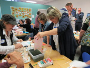 A group of teachers dip paper in dyes